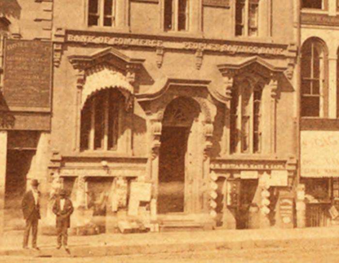 Detail showing the office of the Commerce Bank, beside the Peoples Savings Bank.