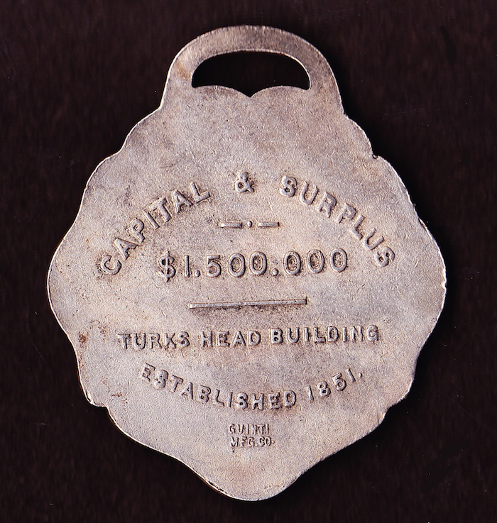 Reverse of Bank of Commerce key fob, showing the Turks Head location.