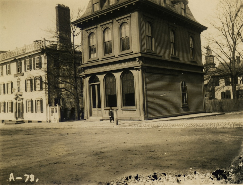 "A photographic print, probably made from a glass plate negative, of the National Exchange Bank (also labeled ""Island Savings Bank"") at 38 Washington Square. The steeple of St. Paul's Methodist Church is visible in the background. © Newport Historical Society. Reprinted with permission."
