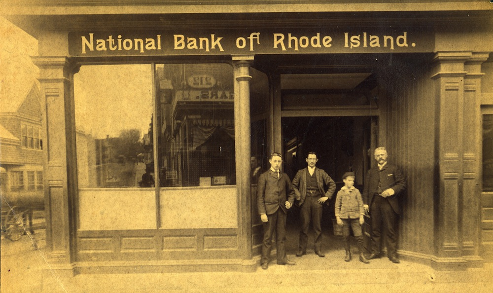 A sepia tone photograph of Arthur H. Popple, John Peckham, an unidentified boy, and Thomas Peckham standing ouside the National Bank of Rhode Island, c. 1890. © Newport Historical Society. Reprinted with permission.